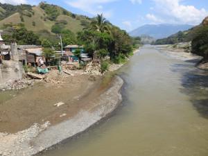 au loin, dans la rivière; une grue charge un camion